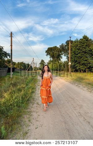 A barefoot girl is running along the village pathway with a fluttering retro dress and hair stock photo