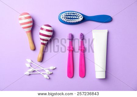 Flat lay composition with baby toothbrushes and toiletries on color background stock photo