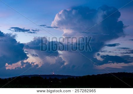 Huge cumulonimbus clouds at blue hour reflecting some of the last glows of the set sun. stock photo