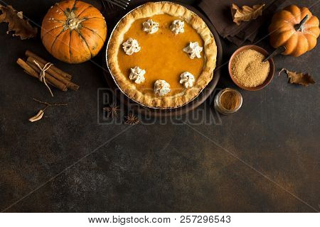 Pumpkin Pie with whipped cream and cinnamon on rustic background, top view. Homemade pastry for Thanksgiving traditional Pumpkin Pie. stock photo