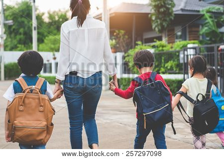 Group Of Mother And Kids Holding Hands Going To School With Schoolbag. Mom Bring Children Walk To Sc