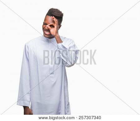 Young arabic african man wearing traditional djellaba over isolated background doing ok gesture with hand smiling, eye looking through fingers with happy face. stock photo