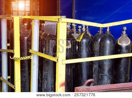 Black cylinders with oxygen are at the factory in the shop, a sunset is breaking through the window, cylinders stock photo