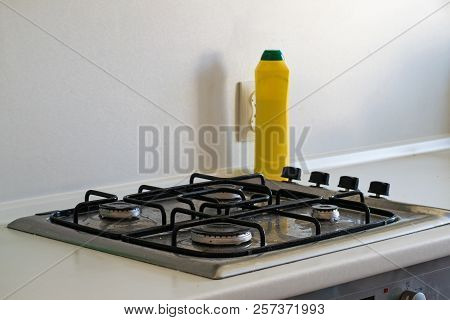 Very dirty gas stove. Cleaning the gas stove with a cleaning agent. stock photo