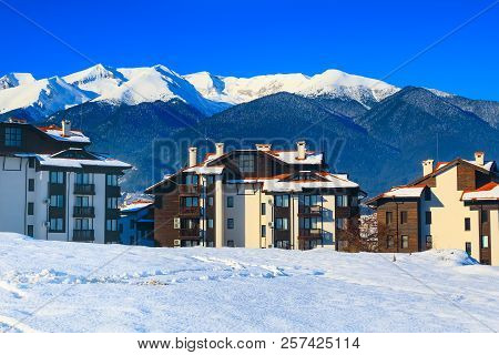 Wooden chalet, houses and snow mountains landscape panorama in bulgarian ski resort Bansko, Bulgaria stock photo