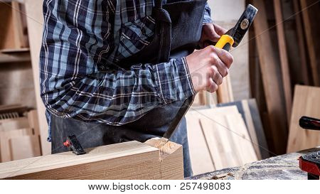 Strong carpenter  in work clothes  carving wood using a woodworking tool, chisel, hands close up, carpentry and craftsmanship concept stock photo