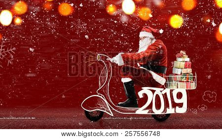 Santa Claus on scooter delivering Christmas or New Year 2019 gifts at snowy red background stock photo