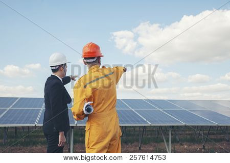 Clean Energy Concept.Worker and professional manager point at solar panels background.Engineer wear safety helmet discuss with Foreman wear orange safety suit and holding blue print at power plant stock photo