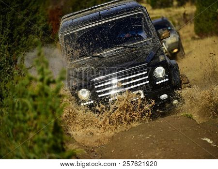 Auto racing on fall nature background. Competition, energy and motorsport concept. Car racing in autumn forest. Off road vehicle or SUV crossing puddle with dirt splash. stock photo