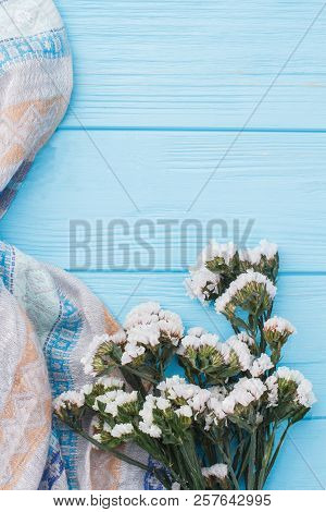 Statice white flowers and cloth. Blue wooden table background. stock photo