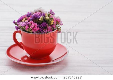 Limonium statice flowers bouquet in coffee mug. White wood background. stock photo