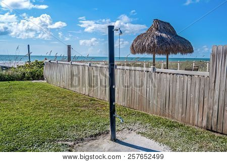 Beach shower close to the beach next to a fenced property on a sunny day. Clearwater Beach, Florida, USA. stock photo