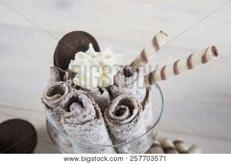 Rolls of ice cream with crushed chocolate cookies. Fresh fried ice cream, ice roll on a light wooden background stock photo
