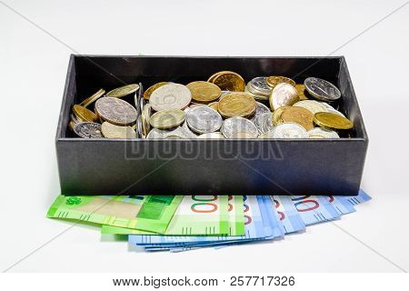 Coins of different denominations in a piggy bank box. Paper rubles under the piggy bank. New banknotes of Russia. stock photo