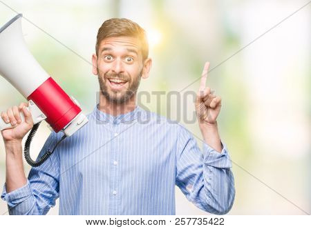 Young handsome man yelling through megaphone over isolated background surprised with an idea or question pointing finger with happy face, number one stock photo