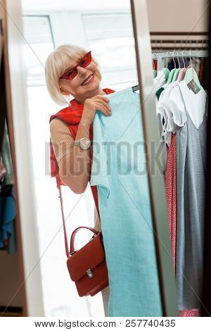 Good looking grey haired woman in fitting room of clothing store stock photo