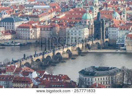 View of Charles Bridge, Old Town Bridge Tower and Church of St. Francis of Assisi. Beautiful Prague cityscape with classic red roofs, Vltava river and famous Czech showplaces. stock photo
