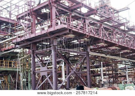 A large iron metal piping trestle with pipes and electric wires and equipment at the petrochemical refinery industrial refinery. stock photo