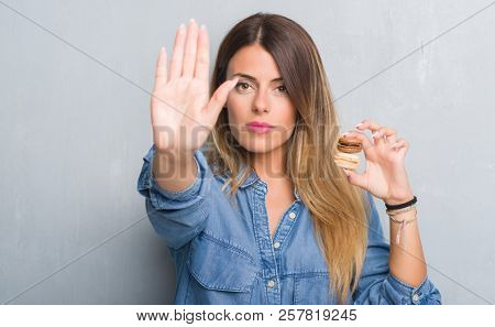 Young adult woman over grey grunge wall eating chocolate macarons with open hand doing stop sign with serious and confident expression, defense gesture stock photo