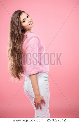 A beautiful and cute young lady posing over pink background. Fashion concept. stock photo