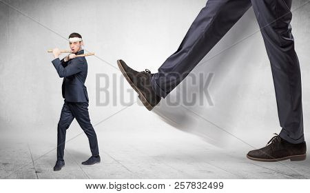 Big foot trample young suited karate man stock photo