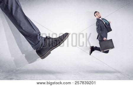 Boss mobbing his worker, illustrated by black shoe kicking small businessman who is flying away in the space stock photo