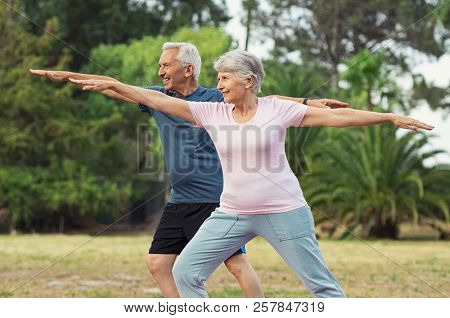 Senior couple doing sport and physical exercises outdoor. Active senior man and elderly woman doing
