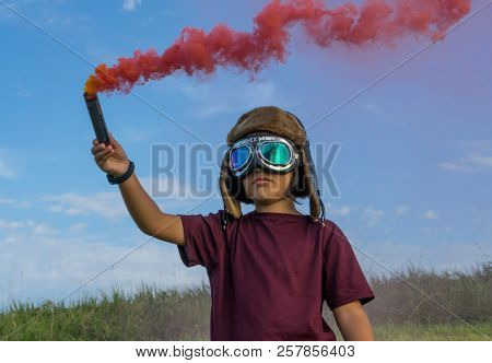 Airborne, Little boy wearing helmet and aircraft googles standing on a green field with colorful smoke, pretending to be a pilot stock photo