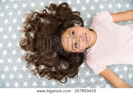 Girl child with long curly hair lay on bed top view. Child perfect curly hairstyle looks cute. Conditioner mask organic oil keep hair shiny and healthy. Amazing curls tips. Make it curly but natural. stock photo