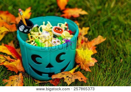 Halloween teal basket full of non-food treats. Halloween Party Favors for kids with food allergy. Teal pumpkin. the concept of health for children in the Halloween season stock photo