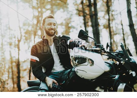 Motorcycle Biker Stops On Highway In A Forest. Speed Vehicle. Cool Rider With A Leather Jacket. Motorbike Concept. Classic Style. Ready To Drive. Speed Motorcycle In A Forest. Quick Driver. stock photo