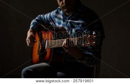 caucasian male musician playing guitar on stage, focus on hand. stock photo