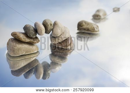 arch of balanced pebbles and stepping stones in the water with reflection, light blue sky with clouds, copy space, selected focus, narrow depth of field stock photo