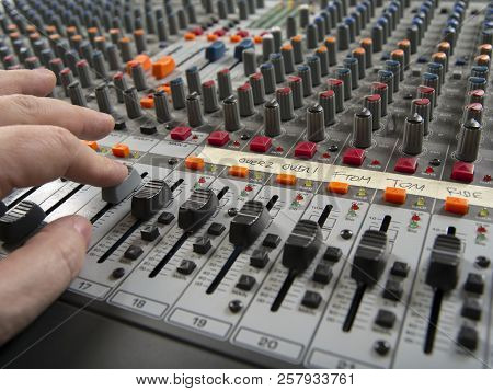 Photo of a person moving faders on a recording studio mixer. stock photo