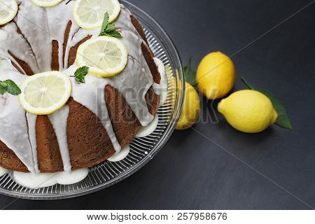 Whole lemon cream cheese bundt cake with slices of fresh lemons and mint on top. Extreme shallow depth of field with selective focus on cake. stock photo