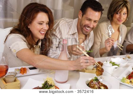 Group of attractive people eating and socializing at a restaurant ** Note: Slight blurriness, best at smaller sizes stock photo