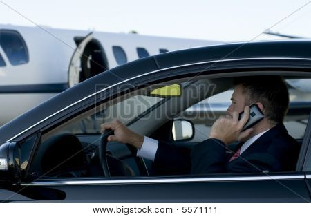 Businessman on his cell phone in luxury car in front of a corporate jet stock photo