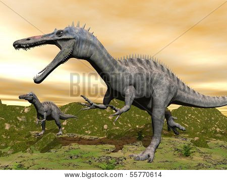 Two suchomimus dinosaurs in nature with green grass by colorful sunset stock photo