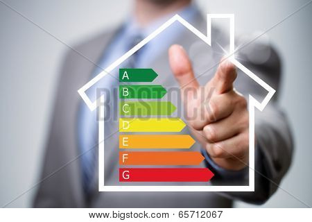Businessman pointing to energy efficiency rating chart and house icon concept for performance, effic
