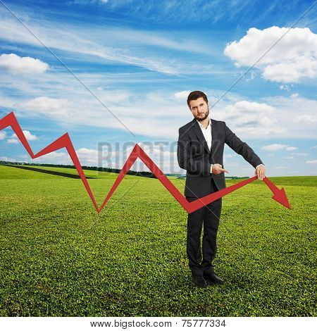 sad broker holding and pointing at falling down graph. photo at outdoor stock photo
