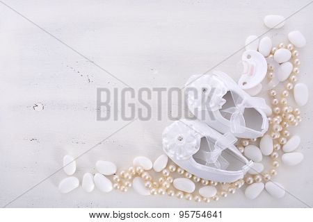 Baby shower neutral white background with baby booties pearls and sugar almonds on shabby chic rustic wood table with copy space. stock photo