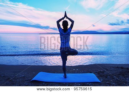 Woman Meditating In Pose Of Tree In The Morning