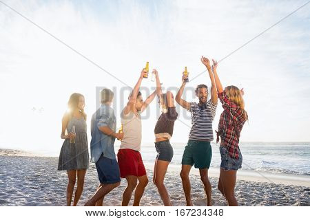 Happy friends dancing together on the beach stock photo