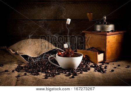 coffee art composition: scattered roasted beans from a bag coffee grinder with ground coffee and a cup of coffee with a splash of falling sugar. in fragrant smoke from coffee. on sackcloth stock photo