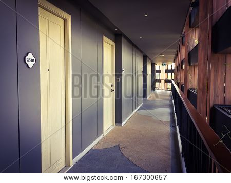 Corridor in hotel building with apartment rooms and windows grey walls and beige doors stock photo