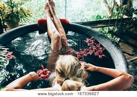 Woman relaxing in round outdoor bath with tropical flowers. Organic skin care in kawa hot bath in luxury spa resort. stock photo