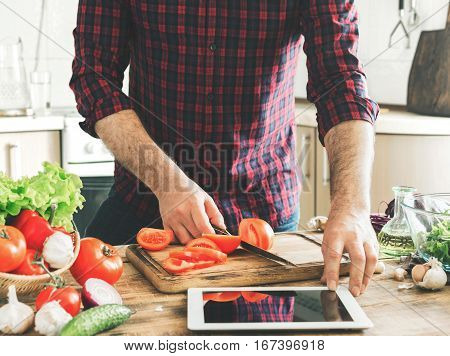 Man following recipe on digital tablet and cooking tasty and healthy food in kitchen at home on a sunny day
