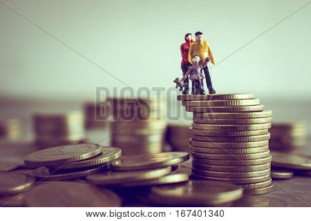 Miniature Mum Dad and Kids standing on top of the money save money concept. stock photo