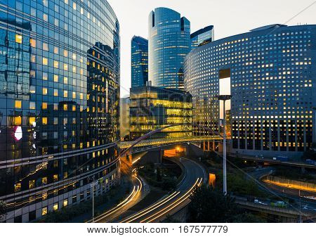 Night architecture - skyscrapers with glass facade. Modern buildings in Paris business district. Evening dynamic traffic on a street. Concept of economics financial. Copy space for text. Toned