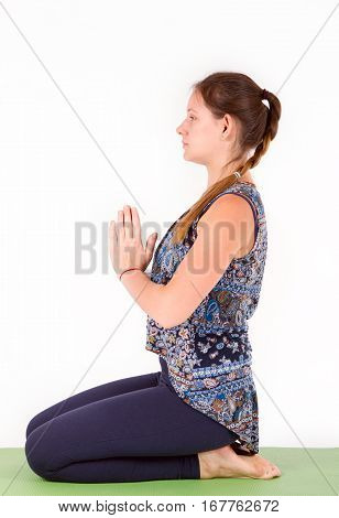Young woman practicing yoga, sitting in seiza exercise, vajrasana pose, working out, wearing sportswear. Meditating or breathing in vajrasana. Full length. isolared stock photo